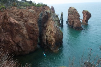 Kayakers explore the 'Three Sisters' rock formations that rise from the waters of the Bay of Fundy at Cape Chignecto Provincial Park